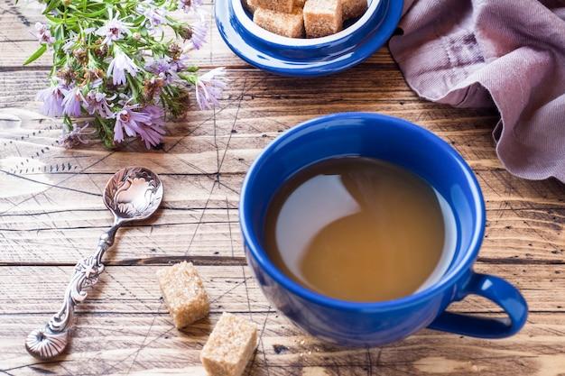 Xícara de café preto fumegante quente com cubos de açúcar na mesa de madeira