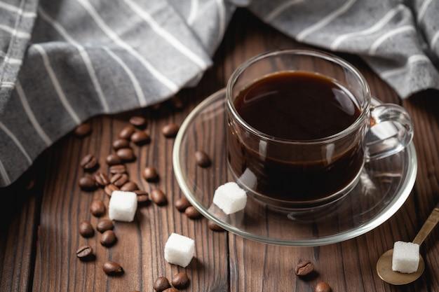 Xícara de café preto na mesa de madeira.