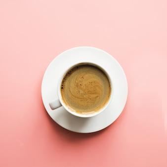 Xícara de café preto na superfície rosa