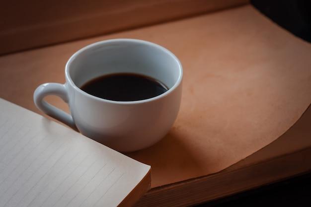 Xícara de café preto perfumado quente da manhã fica em um livro aberto. cores quentes castanhas claras. foco seletivo.