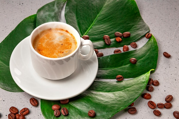 Xícara de café preto quente e grãos de café na folha monstera close-up.