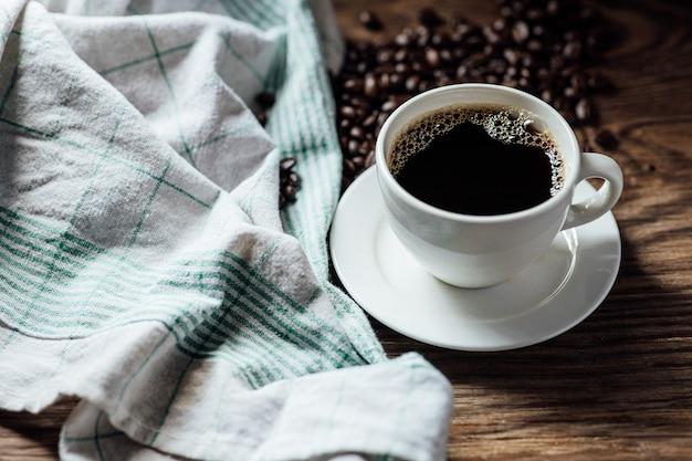 Xícara de café preto quente e grãos de café na mesa de madeira com luz natural pela manhã