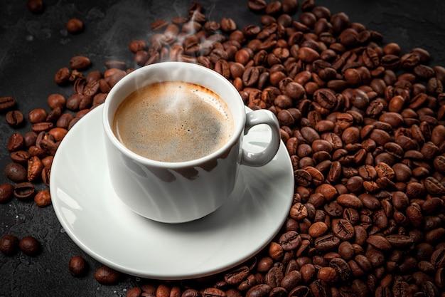 Xícara de café preto quente e grãos de café torrados close-up.