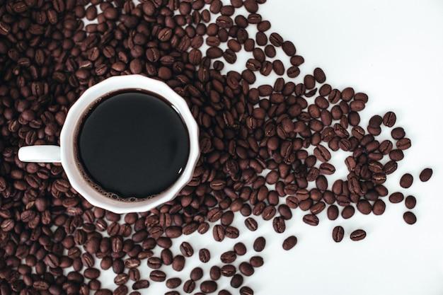 Xícara de café preto quente em pé sobre grãos de café torrados aromáticos frescos isolados no fundo branco
