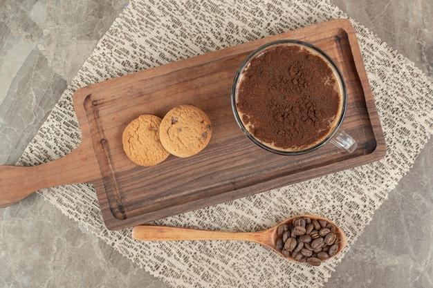 Xícara de café quente, biscoitos na tábua de madeira com grãos de café