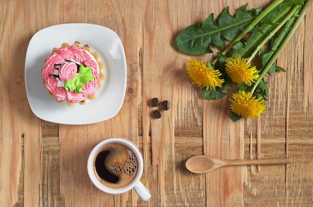 Xícara de café quente, bolo doce e flores no antigo fundo de madeira, vista superior