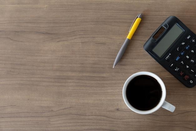 Xícara de café quente, caneta e calculadora preta sobre fundo de mesa de madeira. vista do topo