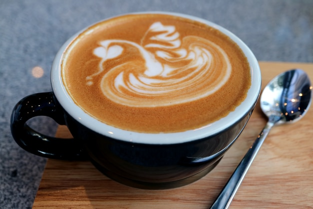 Xícara de café quente cappuccino com colher de chá, servido na bandeja de madeira