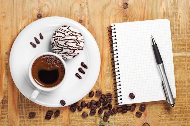 Xícara de café quente com biscoitos saborosos e caderno aberto na velha mesa de madeira