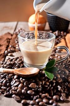 Xícara de café quente com bolinhos, grãos de café e canela