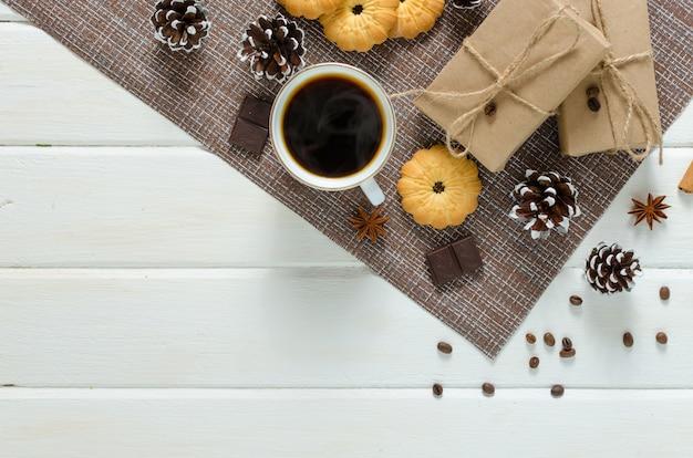 Xícara de café quente com bolos, pacotes de ano novo e pinhas