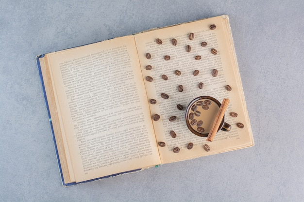 Xícara de café quente com grãos de café em livro aberto.