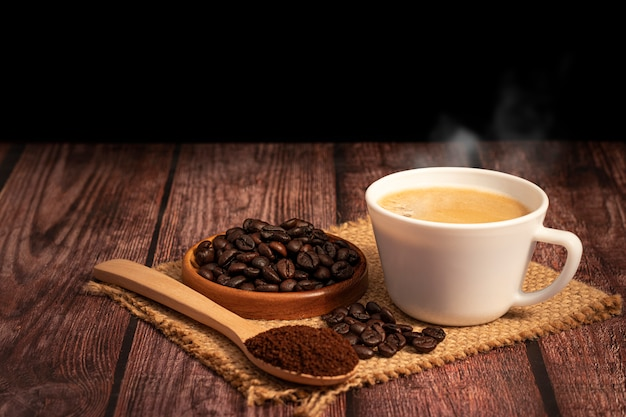 Xícara de café quente com grãos de café orgânicos na mesa de madeira