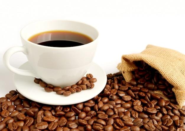 Xícara de café quente com grãos de café torrados espalhados em saco de aniagem