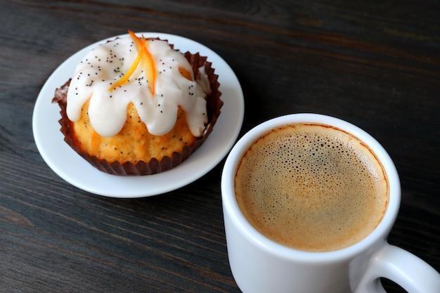 Xícara de café quente com laranja bolo de iogurte de semente de papoula servido na mesa de madeira
