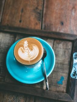 Xícara de café quente com leite arte na mesa de madeira vintage.