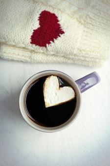 Xícara de café quente com marshmallow de coração e luvas quentes na mesa de madeira clara, close-up