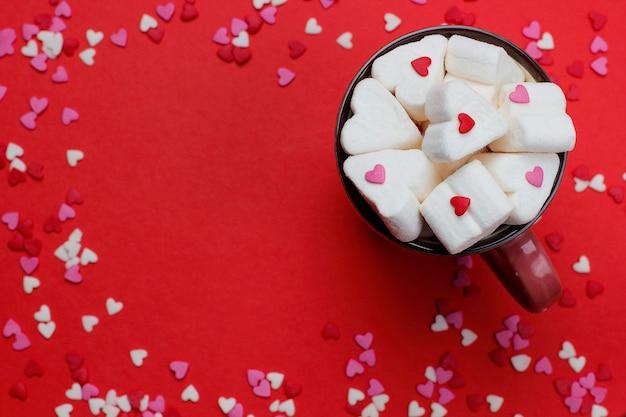 Xícara de café quente com marshmallows em forma de coração e confetes no vermelho
