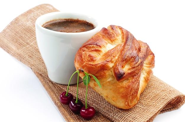 Xícara de café quente com pão e cereja no branco