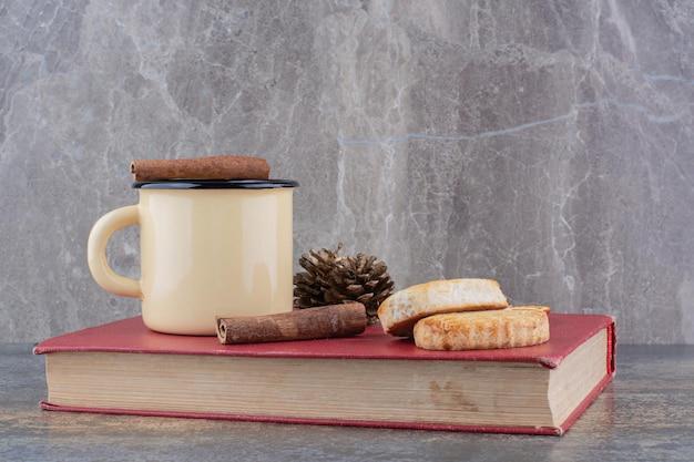 Xícara de café quente com pau de canela e biscoitos no livro. foto de alta qualidade