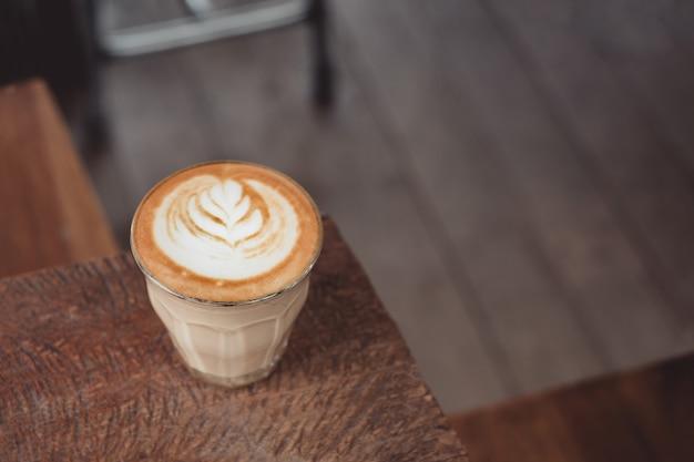 Xícara de café quente de cappuccino na bandeja de madeira com latte art na mesa de madeira no café