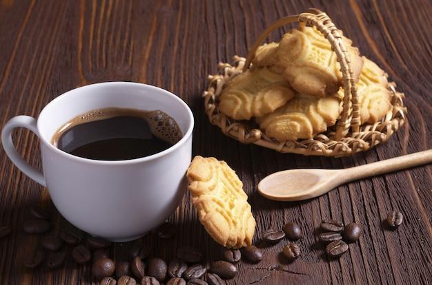 Xícara de café quente e biscoitos amanteigados na mesa de madeira marrom