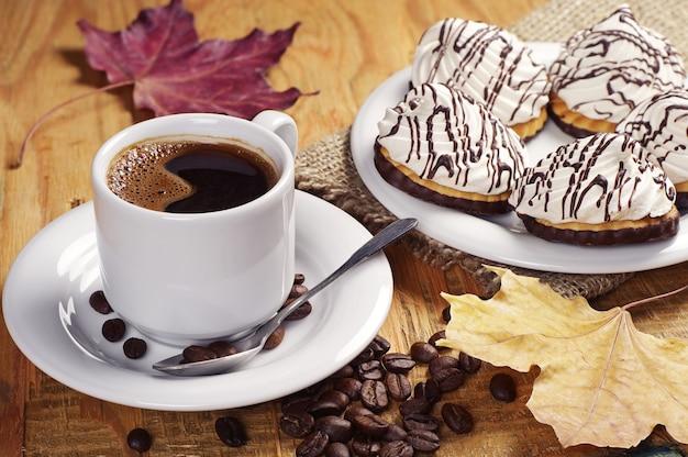 Xícara de café quente e biscoitos com marshmallow na velha mesa de madeira