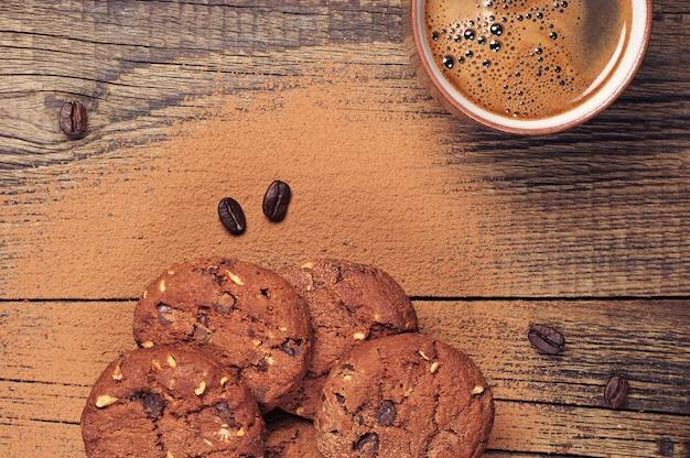 Xícara de café quente e biscoitos de chocolate com nozes na velha mesa de madeira