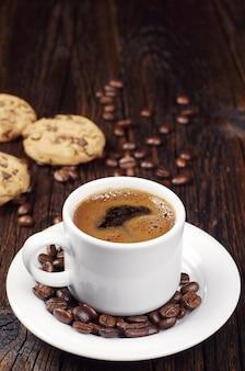 Xícara de café quente e biscoitos de chocolate na mesa de madeira vintage