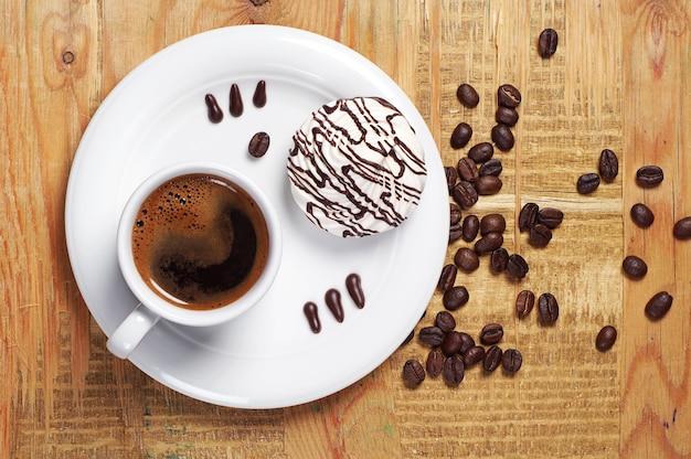 Xícara de café quente e biscoitos de creme na velha mesa de madeira