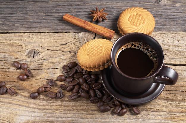 Xícara de café quente e biscoitos saborosos com recheio de creme na velha mesa de madeira