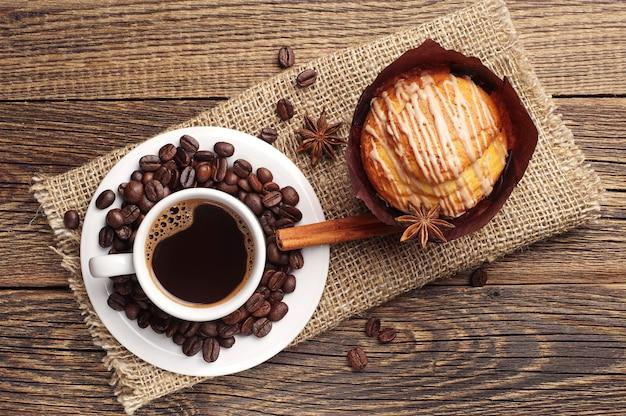 Xícara de café quente e bolinho delicioso na velha mesa de madeira vista superior