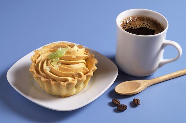 Xícara de café quente e bolo com creme e geléia na mesa azul