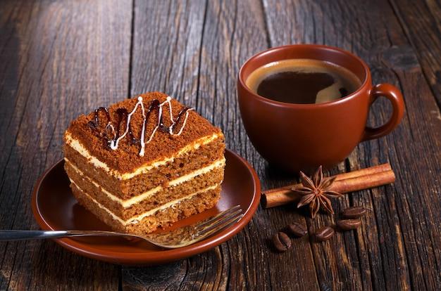 Xícara de café quente e bolo de mel na mesa de madeira escura