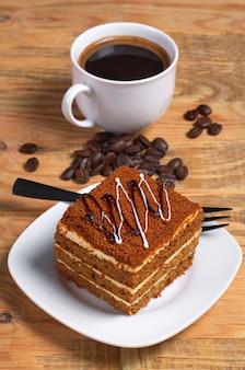 Xícara de café quente e bolo de mel na velha mesa de madeira