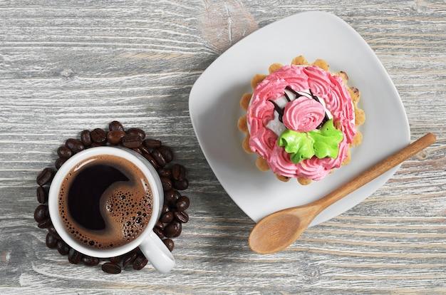 Xícara de café quente e bolo em fundo de madeira velho, vista superior