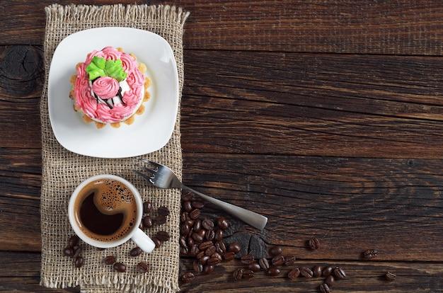 Xícara de café quente e bolo no fundo escuro de madeira, vista superior