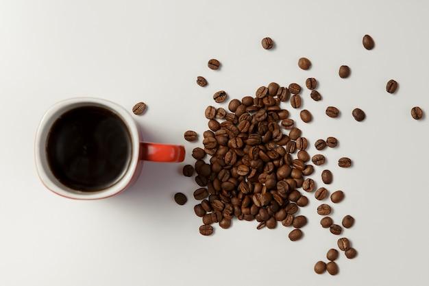 Xícara de café quente e café em grão na mesa branca.