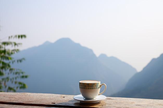 Xícara de café quente é colocada em um terraço de madeira e fundo de montanha
