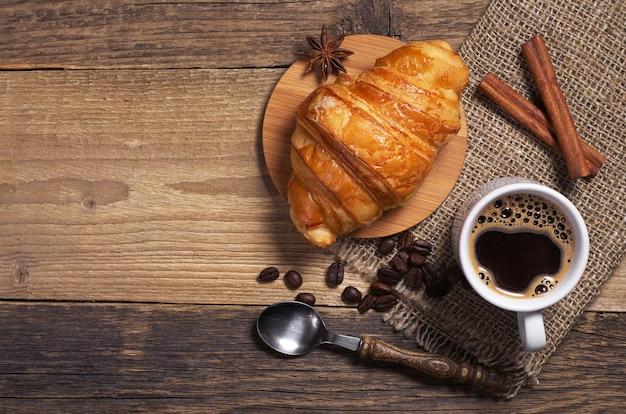 Xícara de café quente e croissant fresco na velha mesa de madeira
