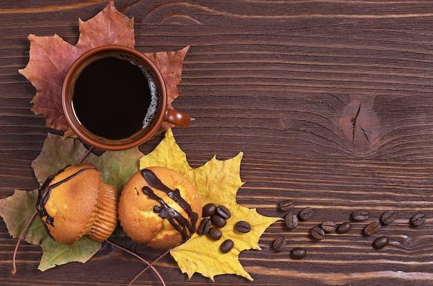 Xícara de café quente e dois cupcakes doces na mesa de madeira, vista superior