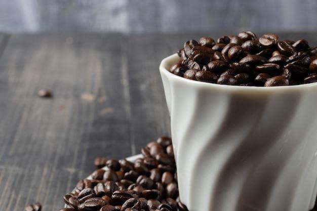 Xícara de café quente e grãos de café torrado
