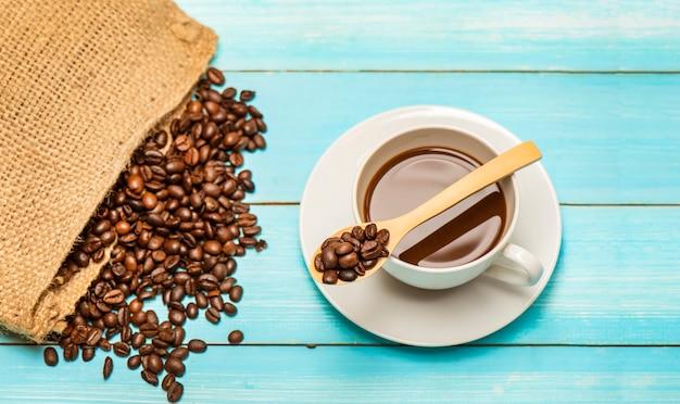 Xícara de café quente e grãos de café torrados do saco saco em uma mesa de madeira e colher.