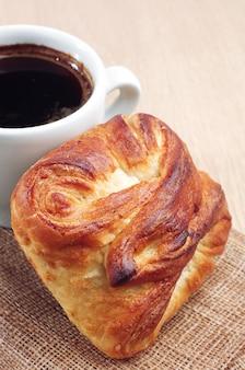 Xícara de café quente e pão doce na mesa de madeira