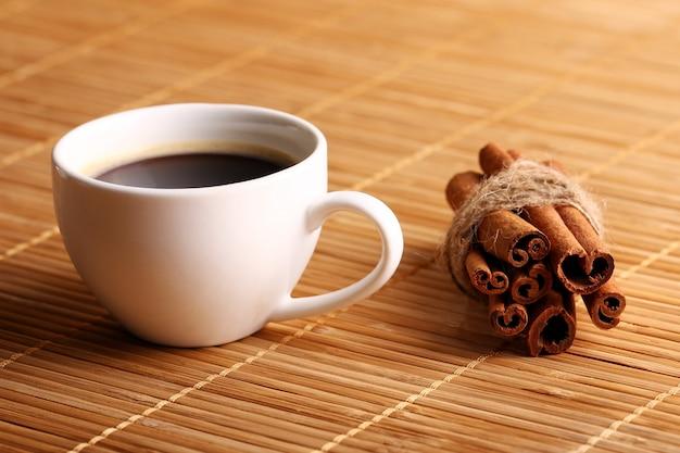 Xícara de café quente e paus de canela