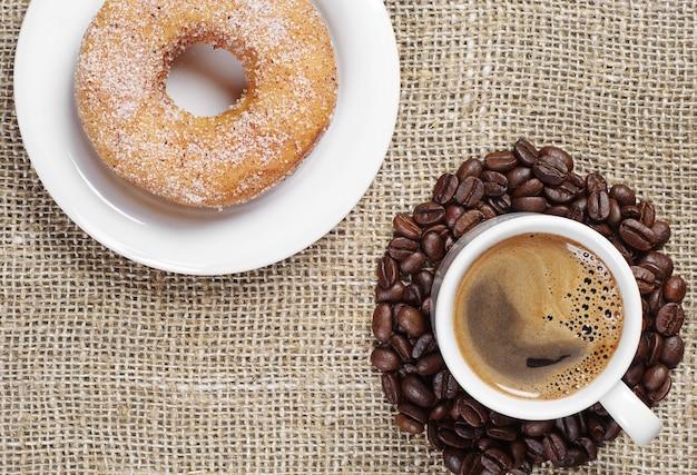 Xícara de café quente e rosquinha doce em um fundo de estopa