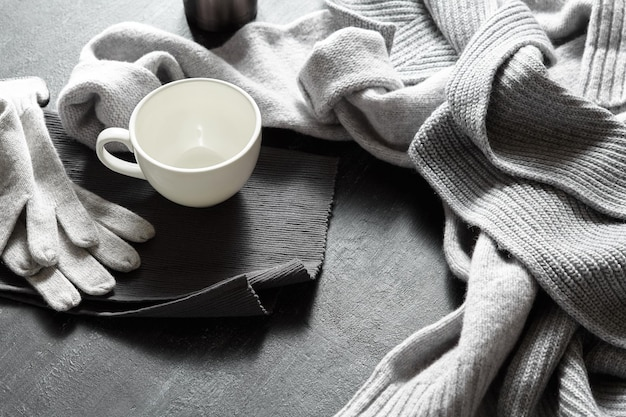 Xícara de café quente em uma mesa preta com suéter quente