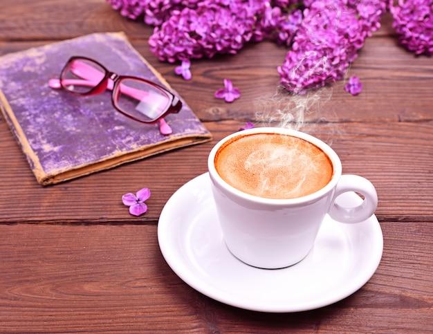Xícara de café quente em uma superfície de madeira marrom