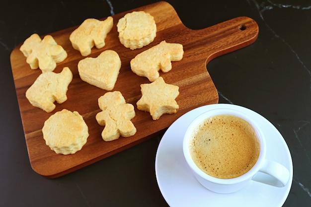 Xícara de café quente espumoso com adorável animal em forma de biscoito sortido na mesa preta