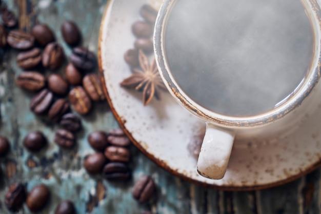 Xícara de café quente fumegante na mesa de madeira